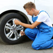 Auto mechanic changing wheel — Stock Photo #30118115