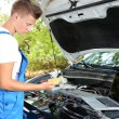 Stock Photo: Professional car mechanic working in auto repair service