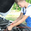 Stock Photo: Young car mechanic uses battery jumper cables to charge dead battery