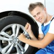 Auto mechanic changing wheel — Stock Photo #30118319