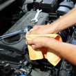 Stock Photo: Motor mechanic cleaning his greasy hands after servicing car