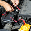 Auto mechanic uses multimeter voltmeter to check voltage level in car battery — Stock Photo #30118805