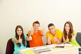 Grupo de jóvenes estudiantes sentados en la sala — Foto de Stock