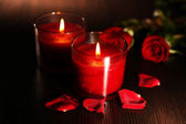 Beautiful romantic red candles with flower petals on dark wooden background — Stock Photo