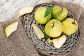 Pears on braided tray on burlap on wooden table — Stock Photo