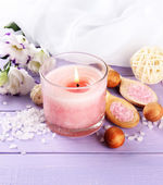 Beautiful pink candle with flowers on purple wooden background — Stock Photo