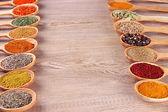 Variedade de especiarias em colheres de madeira com fundo de madeira — Foto Stock