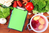 Fresh vegetables and spices and paper for notes, on wooden background — Stockfoto