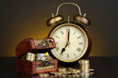 Antique clock and coins on wooden table on dark color background — Stock Photo
