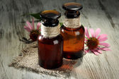 Medicine bottles with purple echinacea flowers on wooden table — Stock Photo