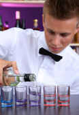 Bartender is pouring vodka into glasses — Stock Photo