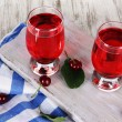 Glasses compote on board on napkin on wooden table — Stockfoto