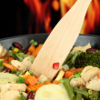 Casserole with vegetables and meat on pan, on fire background — Stock Photo #30237041