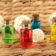 Stock Photo: Bottles with colored liquids on wicker wooden background