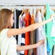 Beautiful young woman thinking what to dress near rack with hangers — Stock Photo