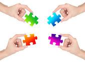 Vier hände halten bunte puzzle, isoliert auf weiss — Stockfoto