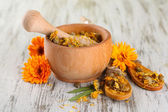 Fresh and dried calendula flowers in mortar on wooden background — Stock Photo