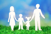 Family from paper on grass on bright background — Stock Photo