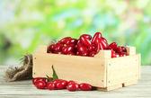 свежий кизил ягоды в деревянный ящик на столе, на открытом воздухе — Стоковое фото
