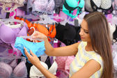 Beautiful young woman in shop with underwear — Stockfoto