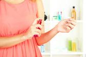 Woman testing perfume on shop windows background — Stock Photo