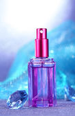 Women perfume in beautiful bottle on blue background — Stock Photo