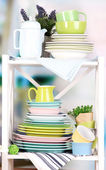 Beautiful white shelves with tableware and decor, on bright background, close-up — Stock Photo