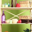 Beautiful white shelves with different home related objects, on color wall background — Stock Photo #30247811