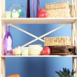 Beautiful white shelves with different home related objects, on color wall background — Stock Photo #30247815