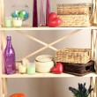 Beautiful white shelves with different home related objects, on color wall background — Stock Photo #30247821