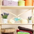 Beautiful white shelves with different home related objects, on color wall background — Stock Photo #30247823