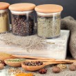 Assortment of spices in wooden spoons and glass jars, on wooden background — Stock Photo #30248411