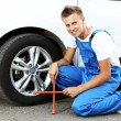 Auto mechanic changing wheel — Stock Photo #30249095