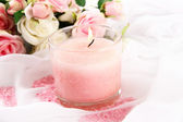Beautiful candle with flowers on white cloth, close up — Stock Photo