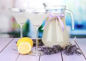 лаванда лимонад в стеклянный кувшин и коктейль очки, на светлом фоне — Стоковое фото