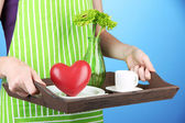 Woman in green apron holding wooden tray with breakfast, on color background — Stock Photo