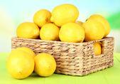 Dojrzałe cytryny w wiklinowym koszu na stole na jasnym tle — Zdjęcie stockowe