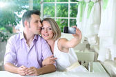 Young couple taking photo with mobile phone in restaurant — Stock Photo