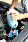 Man pours liquid for washing glasses to car — Stockfoto