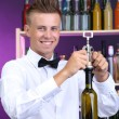 Stock Photo: Bartender opens bottle of wine
