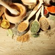 Assortment of spices in wooden spoons and jars, on wooden background — Stock Photo #30313371