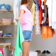 Stock Photo: Beautiful girl throws out unnecessary clothes in room