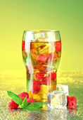 Iced tea with raspberries and mint on bright background — Stock Photo
