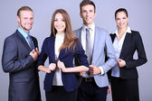 Business team standing in row on grey background — Photo