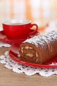 Rollo dulce con taza de té en la mesa en la cocina — Foto de Stock