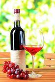 бокалов вина на деревянный стол на фоне природы — Стоковое фото