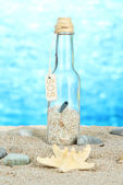 Glass of bottle with note inside on bright blue background — Stock Photo