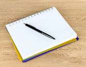 Notebook and pen on wooden table — Stockfoto