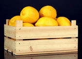 Ripe lemons in wooden box isolated on black — Stock Photo