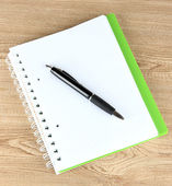 Notebook and pen on wooden table — Stock Photo